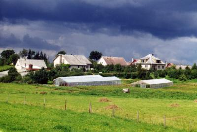 A rather typical scene looking into a small village in Lithuania.  The fields are small and the houses modest, but new techniques such as temporary hot-houses are used to extend the otherwise short growing season.
